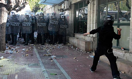 A protester throws a stone at police officers outside the parliament during clashes in Athens