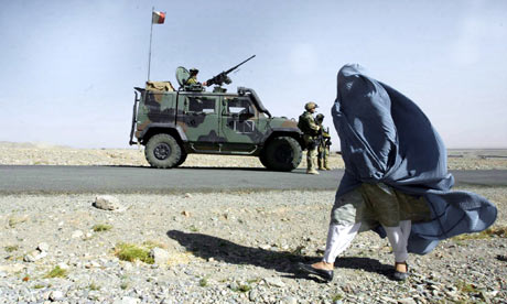 A woman walks past Italian Nato troops in Herat province