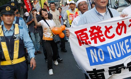 Demonstrators pass the headquarters of Tepco, the operator of Fukushima Daiichi nuclear plant