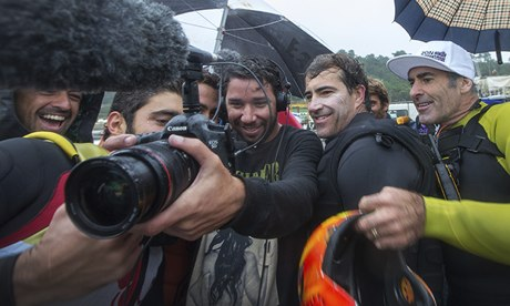 Brazilian surfer Carlos Burle, (2nd r) watches footage of himself suring giant waves in Nazare