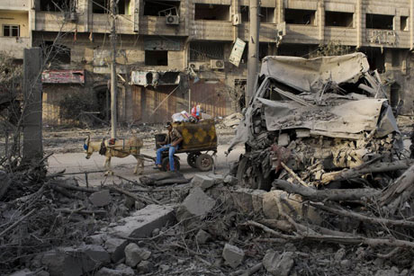 A Palestinian man rides past a destroyed area after an Israeli airstrike