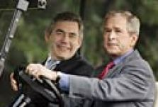 George Bush and Gordon Brown in a golf cart.