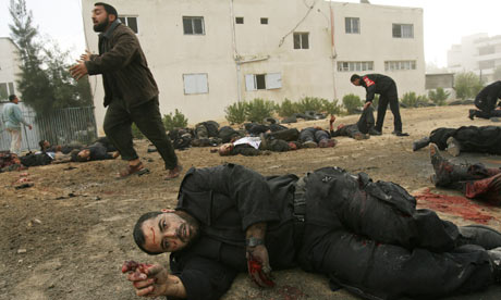 A wounded Palestinian policeman gestures