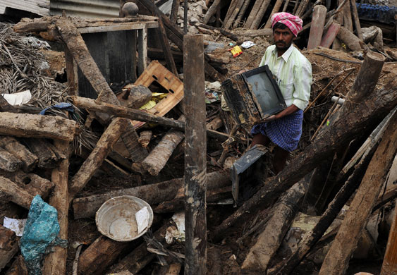 Via Guardian:A flood victim recovers a TV set from his damaged house in Talmari, Karnataka