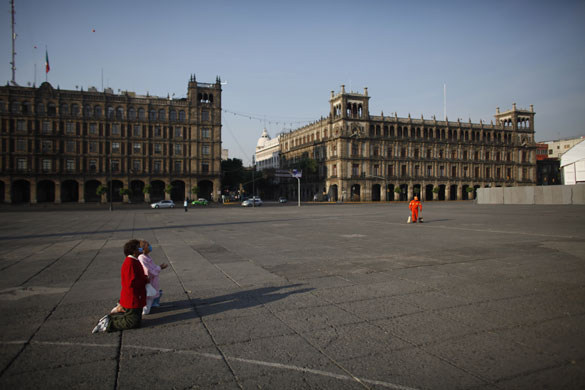 Women kneel in prayer in the center of Mexico Citys Zocalo Plaza.  Usually a bustling tourist center, the plaza is left empty after swine flu threats