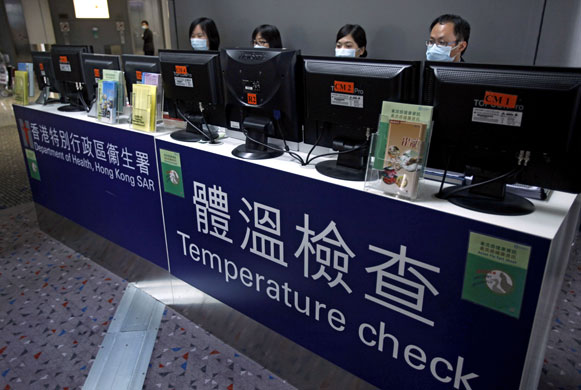 Airport workers monitor passengers from heat-sensitive cameras in Hong Kong, the city at the forefront of disease prevention after the 2003 SARS epidemic