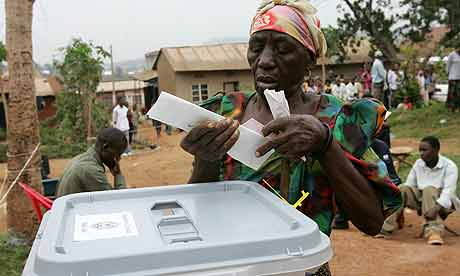 A woman folds her ballot paper at a polling station in Kampala, Uganda, during the 2006 election