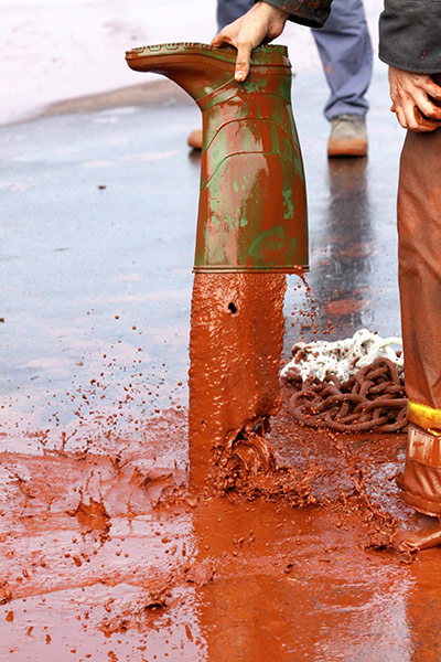 Hungary sludge flood: A firefighter pours mud put of his boot in Devecser