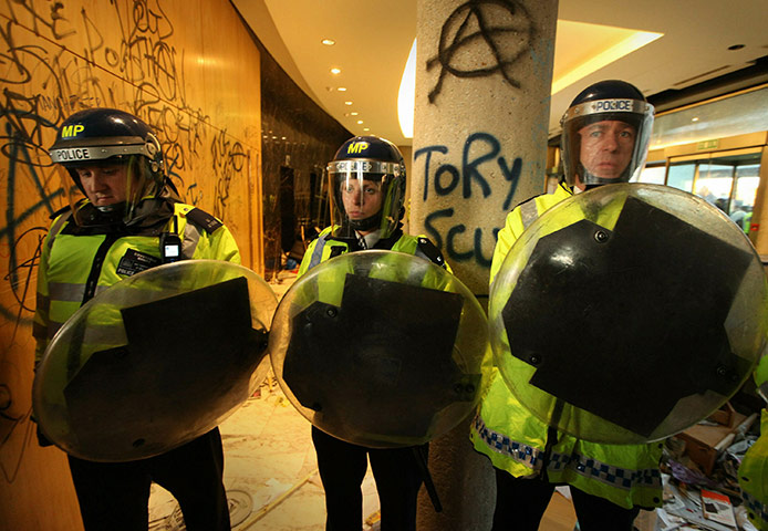 Students protest: Riot police stand guard inside the wrecked entrance to Millbank
