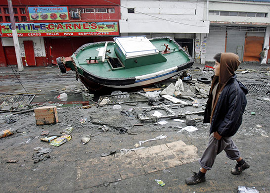 Tsunami damage: A boy walks by a boat drawn from the port into Talcahuano, Chile