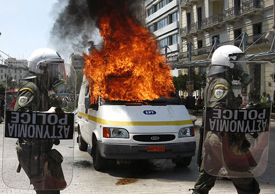 Athens Riot: Police in front of a burning television van during riots in Athens