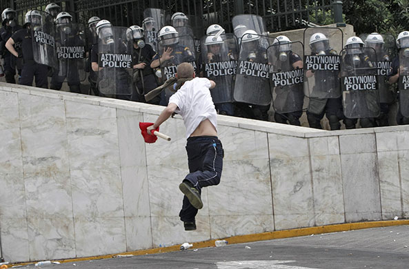Strike in Greece: A demonstrator hurls projectiles at riot police