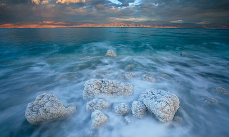 Boulders spiky with salt crystals edge the Dead Sea