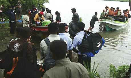 Sri Lankan rescuers evacuate residents of the eastern district of Batticaloa by boat as floods rise