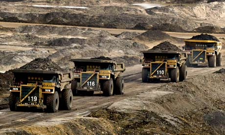 Mining trucks carry loads of oil-laden sand in Canada.