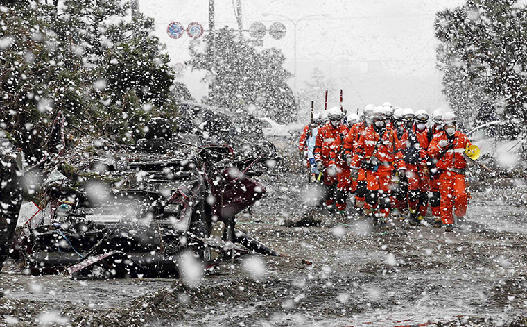 japan disatster: Heavy snow falls on  rescue workers at a devastated factory area in Sendai