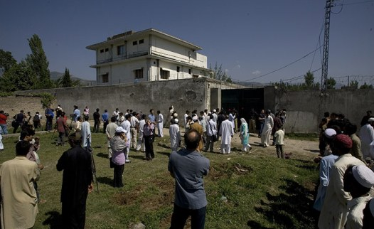 Pakistan : Local people and media gather outside the perimeter wall