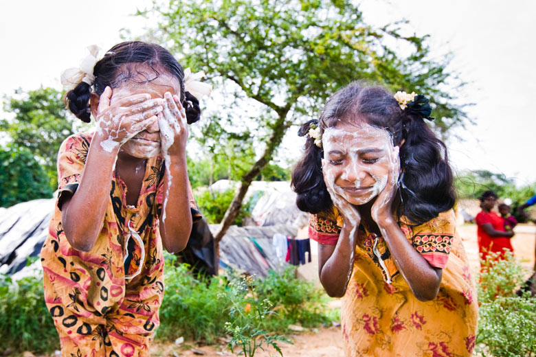 Dalit girls wash their faces in a segregated slum area of Bengaluru