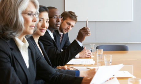 Men and women of different backgrounds sitting at a board table