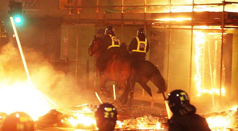 Mounted police patrol the streets as fires burn in Tottenham Photograph: Lewis Whyld/PA