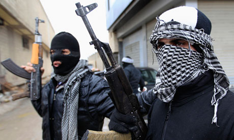 Free Syrian Army fighters patrol a street in the Damascus suburb of Saqba