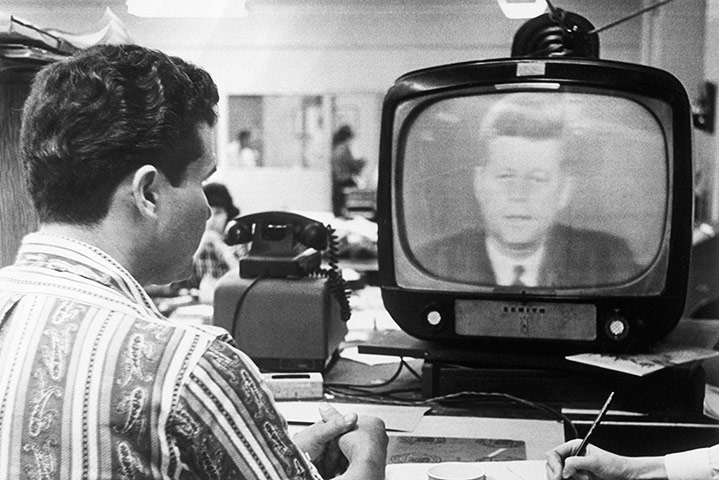 Cuban missile crisis : Cuban man watching President Kennedy speak on TV