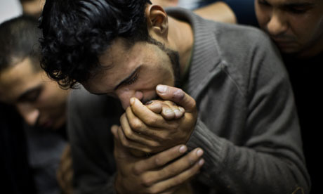 A Palestinian man kisses the hand of a dead relative