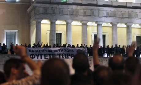 Parliamentary members of the Coalition of the Radical Left (SYRIZA) party hold a banner at the entrance of the Greek Parliament reading 'You destroy the country - Leave now' while waving to the people gathered outside the Parliament in Athens, Greece, 07 November 2012.