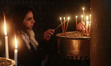 Woman lights a candle at Church