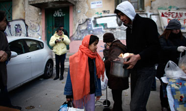 Immigrant families and homeless people receive food from a humanitarian group in Athens, Greece