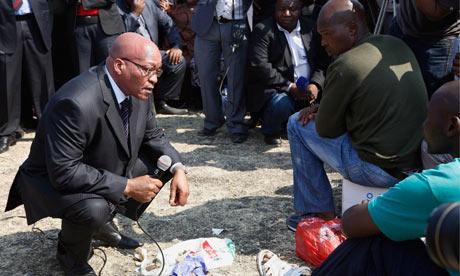 South Africa's President Zuma, left, speaks to striking Lonmin miners