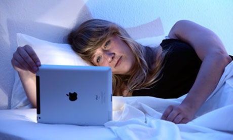 A woman uses an iPad tablet in bed