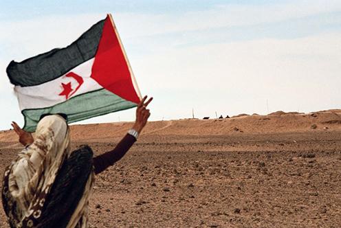 A woman flies the Saharawi flag in Western Sahara