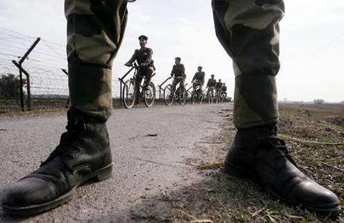 Members of the Indian Border Security Forces patrol along the fence separating India and Bangladesh on bicycles
