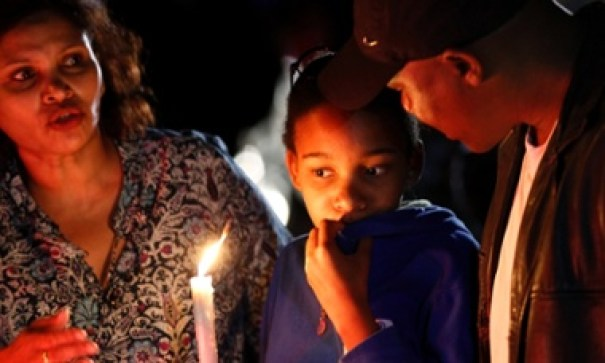 A woman holds a candle outside the house of former South African President Nelson Mandela after news of his death