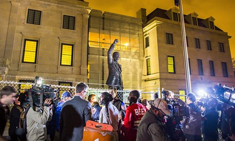 People gathering around a statue of Nelson Mandela at the South African embassy in Washington DC