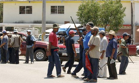 Armed men stand at the entrance to the town of Tierra Colorada, Mexico