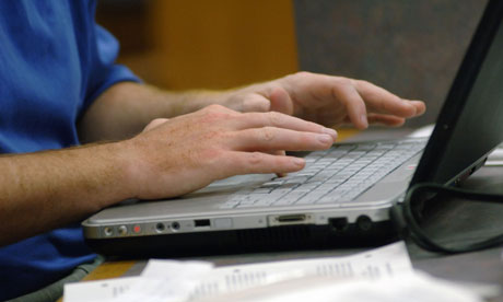 Man's hands typing on laptop keyboard.