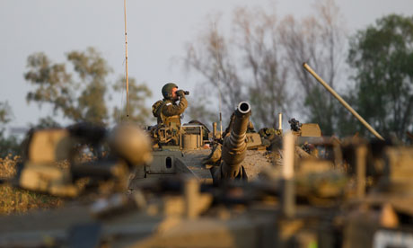 An Israeli soldier looks through his binoculars from the top of his tank