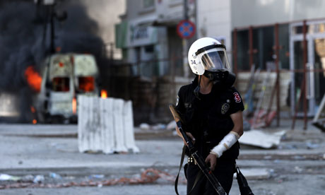 A Turkish riot policeman holds a tear gas grenade launcher in Taksim Square