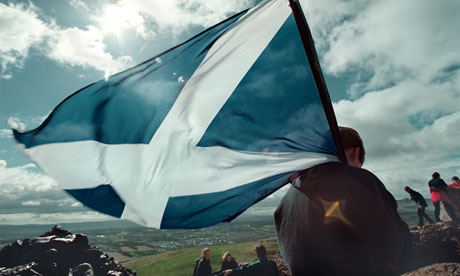 A young Scot bearing the saltire looks down on to Edinburgh from Arthur's Seat