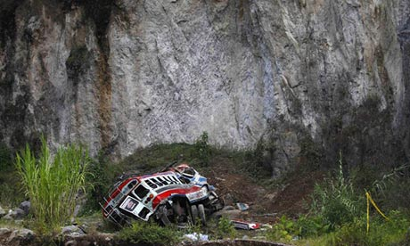 The wrecked bus lies at the bottom of a ravine at San Martin Jilotepeque