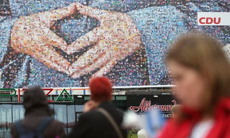 People in Berlin near an election campaign poster of the hands of German chancellor Angela Merkel