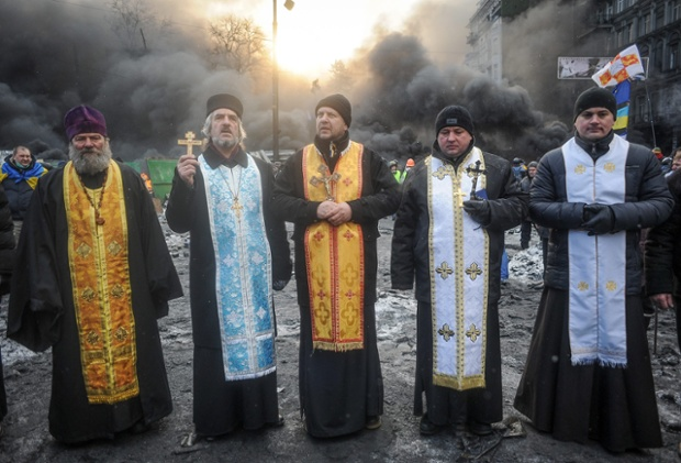 Priests stand in front of the burning barricades. At least two people died of gunshot wounds and a demonstrator also reportedly fell to his death after being chased by police on Wednesday