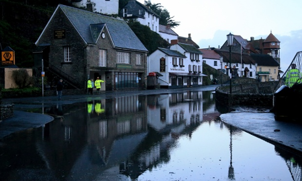 People look at the high tide flood water that still remains on the seafront at Lynmouth in North Devon, England.