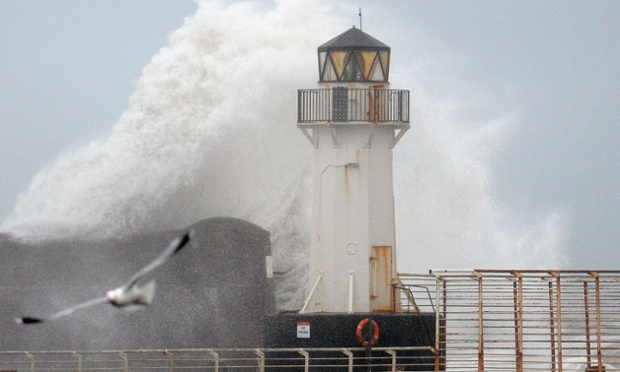 Waves crash over Ardrossan harbour lighthouse in Ardrossan, Scotland.