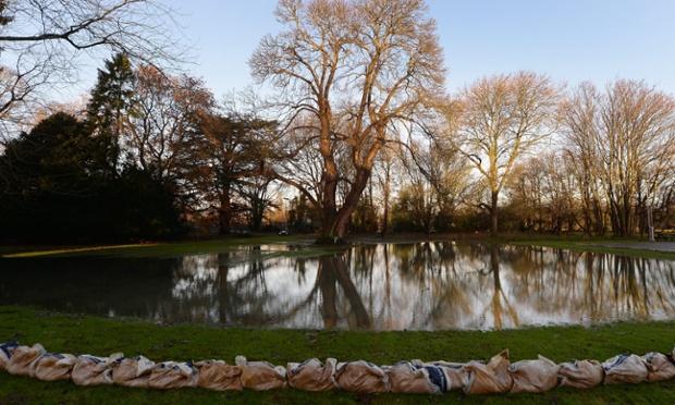 Sandbags line a river bank in Leatherhead, Surrey