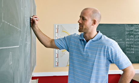 A male teacher writing on a blackboard