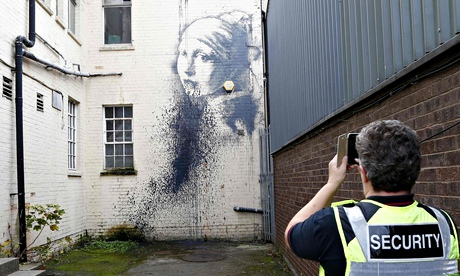 A city council security guard photographs a piece of street art attributed to Banksy in Bristol