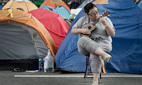 A protestor takes time out to practice the ukulele.